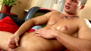 Angelic brunette gay Stefan stroking his enormous oiled cock on the couch