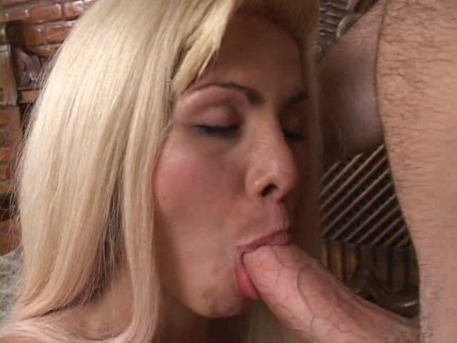Appealing blonde tranny bitch sucking a massive penis on her knees