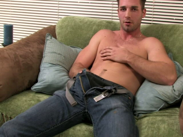 Appealing brunette gay Johnny rubbing his giant phallus on the couch