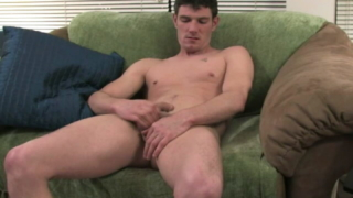 Brawny brunette gay playing with his massive schlong on the couch