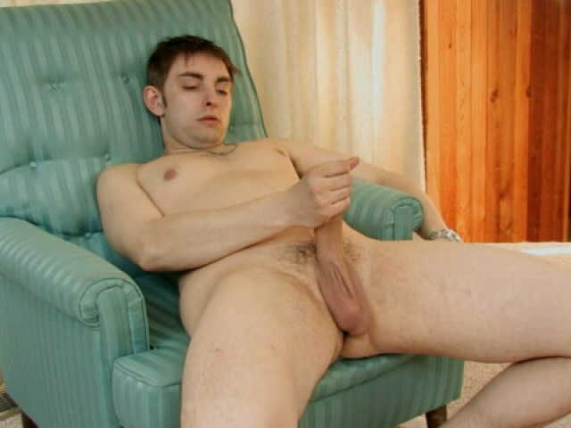 Brown haired young gay Walley jerking his dick on the armchair