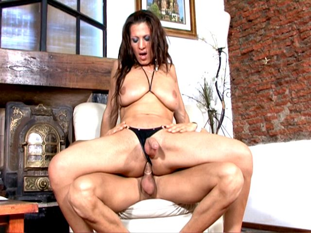 Brunette tranny girl with huge tits Triany riding anally a massive cock on armchair