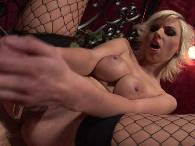 Busty blonde babe in fishnets fucking a large glass dildo on the couch