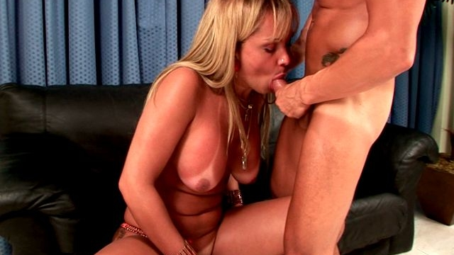 Busty-blonde-shemale-in-boots-dayanne-wanking-cock-white-giving-oral-sex-on-the-couch_01
