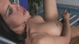 Busty brunette she-male Penelope Jolie masturbating her hard cock at the poolside