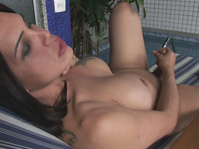 Busty brunette she-male Penelope Jolie masturbating her hard cock at the poolside Shemale Lolipops XXX Porn Tube Video Image