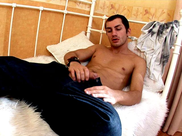 Charismatic brunette gay Tommy jerking off his large penis in the bedroom