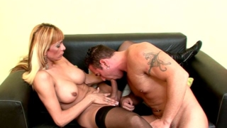 Charming blonde shemale cheerleader Celeste gets big shaft sucked by a tattooed stud on the couch