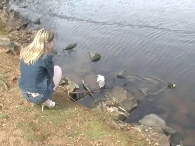 Cute blonde teen girl in mini jeans skirt Kitty Kim posing at the lake Kitty Kim XXX Porn Tube Video Image