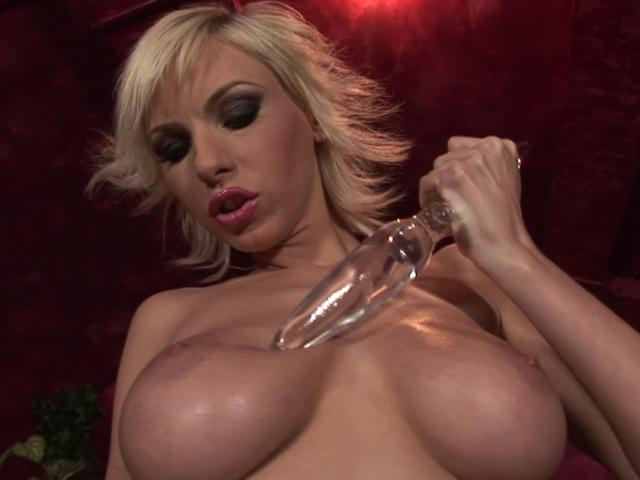 Enchanting blonde vixen with big breasts playing with a glass dildo
