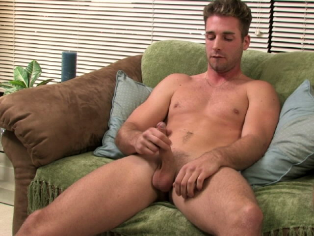 Good looking blonde gay Johnny jerking his large phallus on the couch