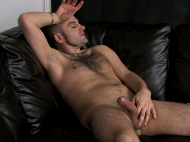 Good looking gay DJ wanking his large penis on the couch