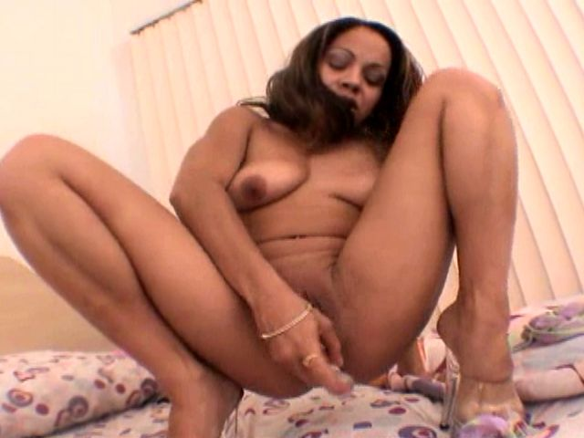 Good looking young black girlfriend Dolly Catholic masturbating her clit with a long glass dildo