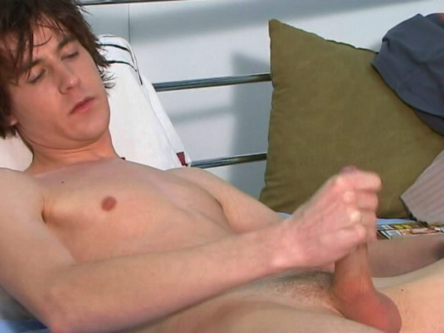 Good looking young gay Ashley wanking his large cock in bedroom