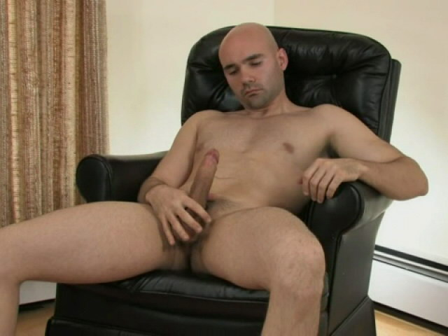 Gorgeous bald gay Bucky masturbating his big penis on the armchair