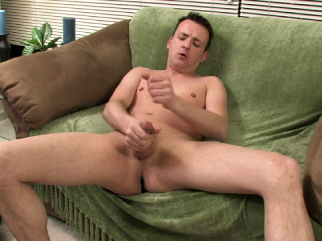 Gorgeous brunette gay Sean rubbing his monster dick on the couch