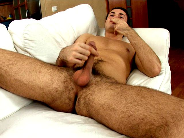 Handsome brunette European twink Duke jerking off his massive penis on the couch