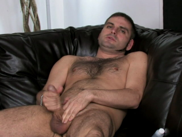 Handsome brunette gay Dj oiling and jerking his big shaft on the couch