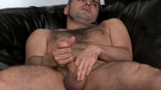Hefty brunette gay Dj masturbating his massive dong on the couch