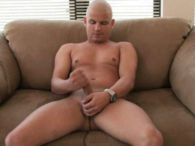Horny bald gay Lance masturbating his thick cock on the couch