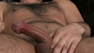 Hot and horny gay Dj masturbating his enormous cock on the couch