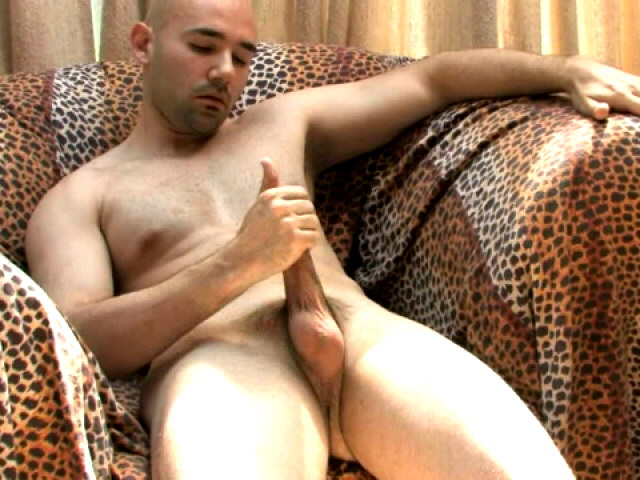 Hot bald gay Bucky wanking his enormous cock hard on the couch