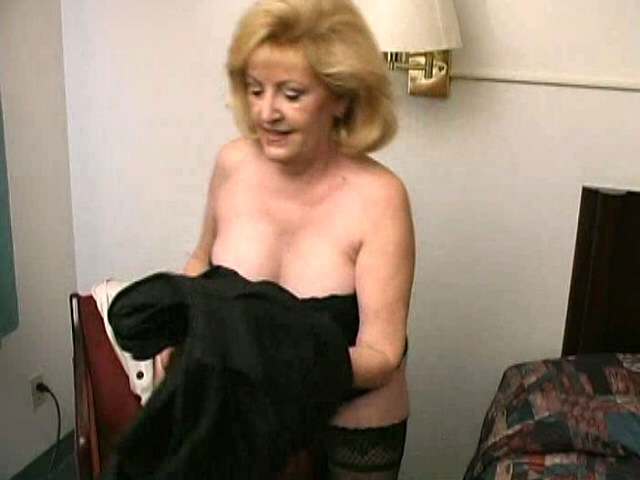 Lustful blonde grandma Kitty Fox stripping and showing her sexy decolletage Is That Grandma XXX Porn Tube Video Image
