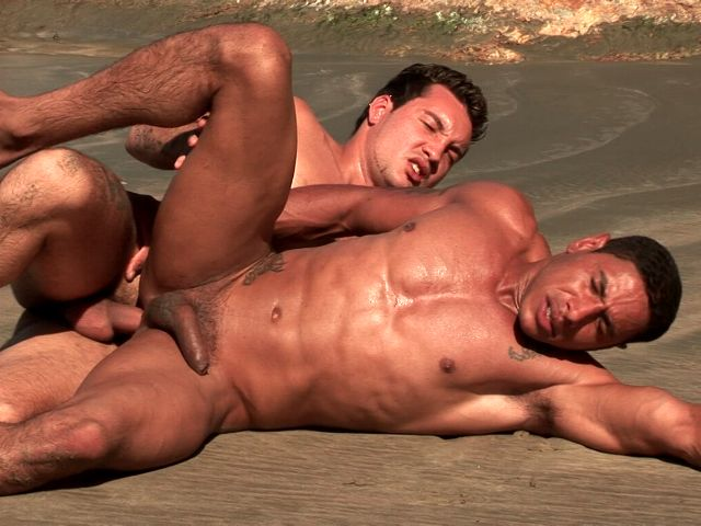 Muscle bodied bronzed gay Alber Charles gets anally smashed from behind by Anthony Gimenez on the beach
