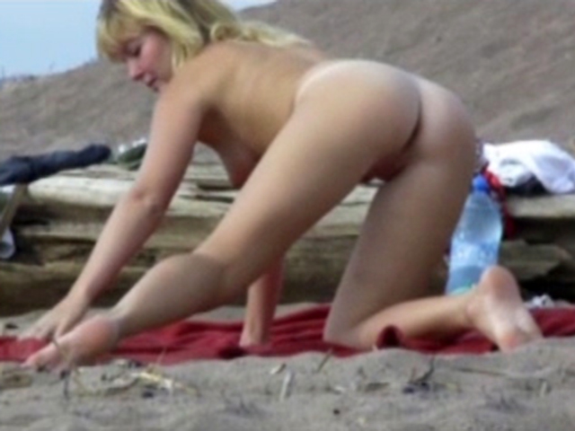 Naked blonde spreads legs at the beach