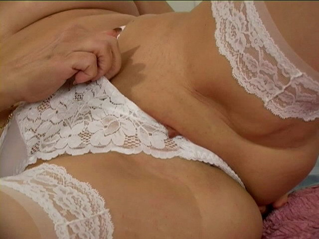 Naughty blonde granny in stockings Leona plays with her tits and wet muff