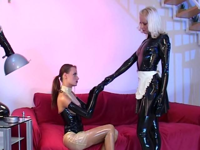 Platinum blonde lesbian slave in latex Petova gets pussy fingered by a hot mistress
