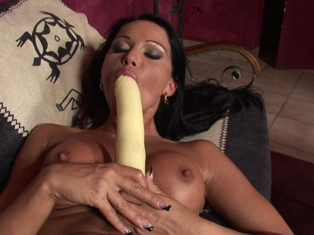 Raven haired goddess with divine jugs licking a massive dildo