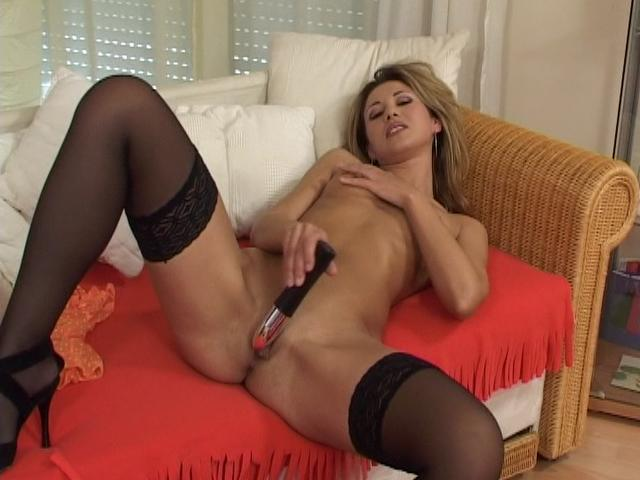 Sensual blonde chick in stockings fucking a big toy on the couch