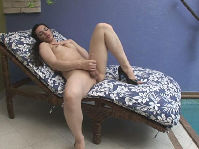 Sensual brunette shemale Thays Dumond masturbating at the poolside