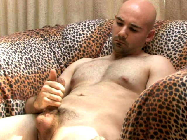 Sexy bald gay Bucky masturbating his enormous penis on the couch