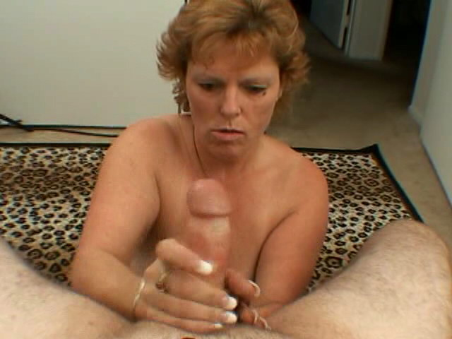Short haired hottie granny Megan wanking a massive cock on her knees