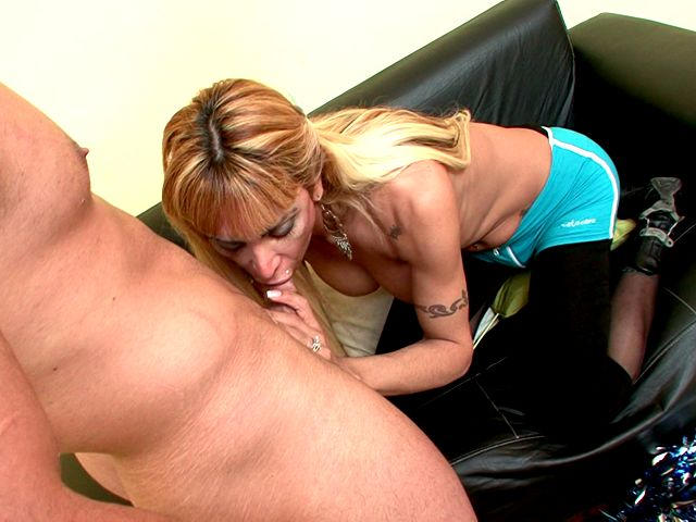 Sinfully blonde shemale cheerleader Celeste sucking a massive penis with lust on the couch