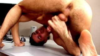 Sweet brunette gay Duke licking his sexy body and wanking cock under briefs at the desk