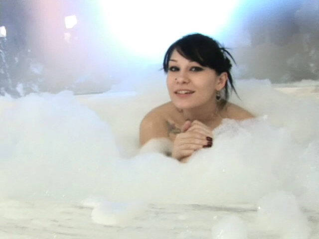 Tattooed brunette babe Jennique invinting us in her bubble bath