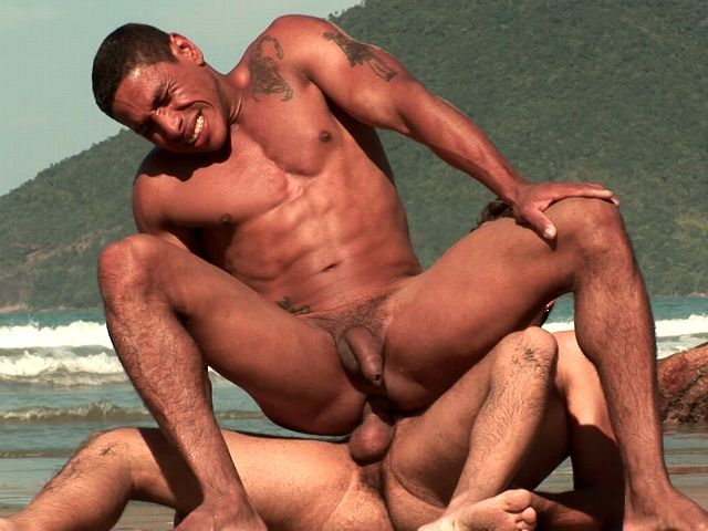 Tattooed gay with sexy bronzed body Alber Charles riding anally Anthony Gimenez's huge schlong on the beach