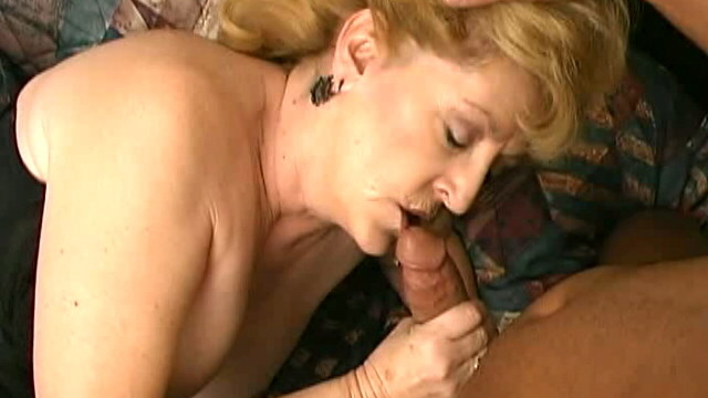 uninhibited-busty-blonde-granny-kitty-fox-sucking-a-large-black-cock-in-bedroom_01