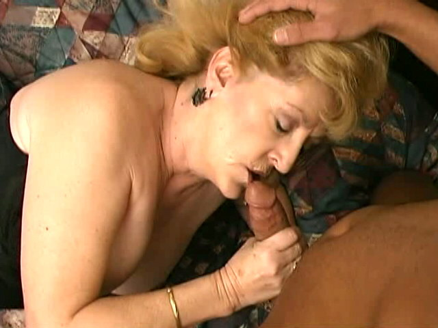 Uninhibited busty blonde granny Kitty Fox sucking a large black cock in bedroom Is That Grandma XXX Porn Tube Video Image