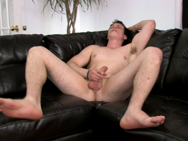 Wild brunette gay Bruce jerking off his massive schlong on the couch